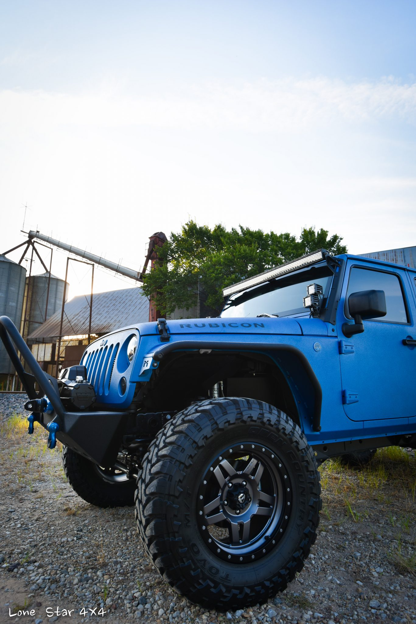 Sprayed Blue Jeep Rubicon Drivers Side View of Front Tire and Hood