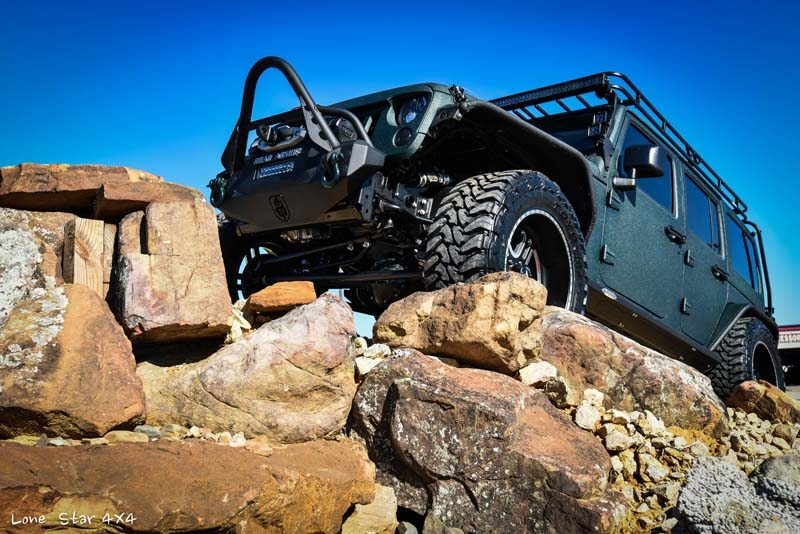 Jaguar Green Jeep Wrangler on Rocky Incline